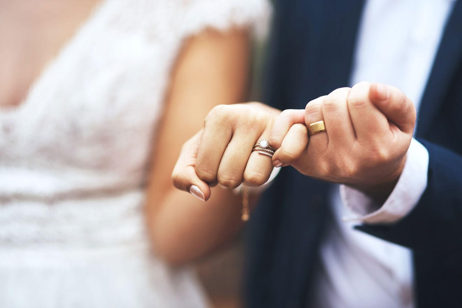 Couple holding hands showing wedding rings.